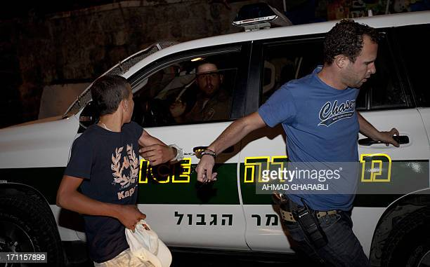 An Israeli policeman in plain clothes arrests a boy in East Jerusalem on June 22 2013 An Israeli border policeman was struck in the face by an object...
