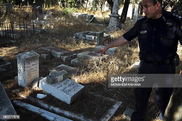 An Israeli policeman inspects a vandalized tombstone at a Christian cemetery located in mount Zion outside Jerusalem's Old City on September 29 2013...