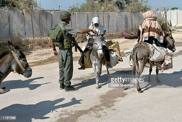 An Israeli policeman questions Palestinian women taking advantage of a lift in the curfew July 22 2002 in the West Bank town of Qalqilya The Israeli...