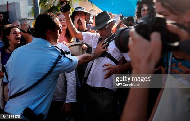 An Israeli policeman scuffles with Israeli left wing activists from the Peace Now movement on September 8 during a protest in front of the house...