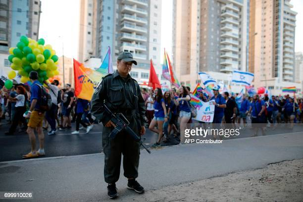 An Israeli policeman stands guard as Israelis take part in the first annual Gay Pride parade in the southern Israeli city of Beersheba on June 22...