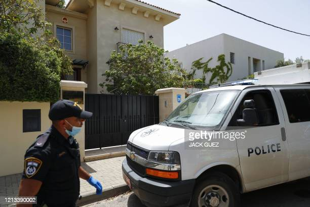 An Israeli policeman stands guard in front of the gated house of the Chinese ambassador where he was found dead, in Herzliya on the outskirts of Tel...