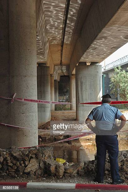 An Israeli policeman stands guard over a cordoned section near the highly polluted Yarkon river during searches for the body of fouryearold...