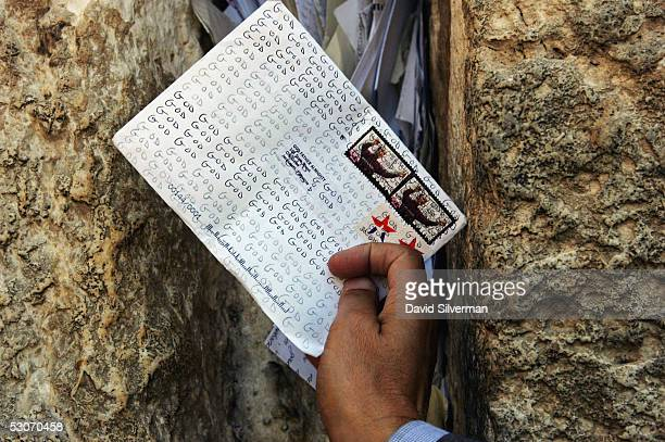 An Israeli Postal Authority worker places a letter to God between the ancient stones of the Western Wall Judaism's holiest site June 15 2005 in...