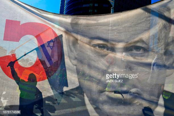 TOPSHOT An Israeli protester wearing a yellow vest carries a national flag during demonstrations against the rising cost of living on December 14 in...