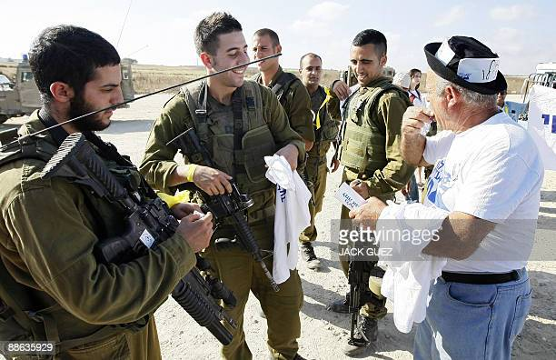 An Israeli protestor distributes tshirts with a portrait of captured soldier Gilad Shalit to Israeli soldiers during a demonstration marking Shalit's...