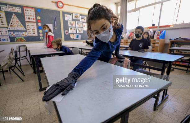 An Israeli pupil wearing protective gear sanitises her desk upon return to school after the COVID19 lockdown at Hashalom elementary in Mevaseret Zion...