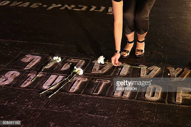 TOPSHOT An Israeli relative of Holocaust victims lays a flower at the Hall of Remembrance where the names of major death and concentration camps are...