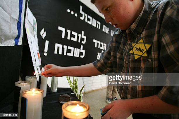 An Israeli schoolboy, wearing a yellow star of David, lights memorial candles during a Holocaust Memorial Day ceremony at the Tali school April 16,...