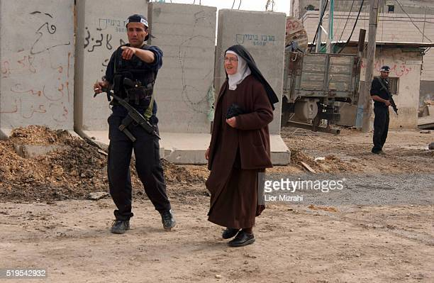 An Israeli security guard gives directions to a christian nun next to the separation wall in the Arab neighborhood of AbuDis in east Jerusalem Sunday...