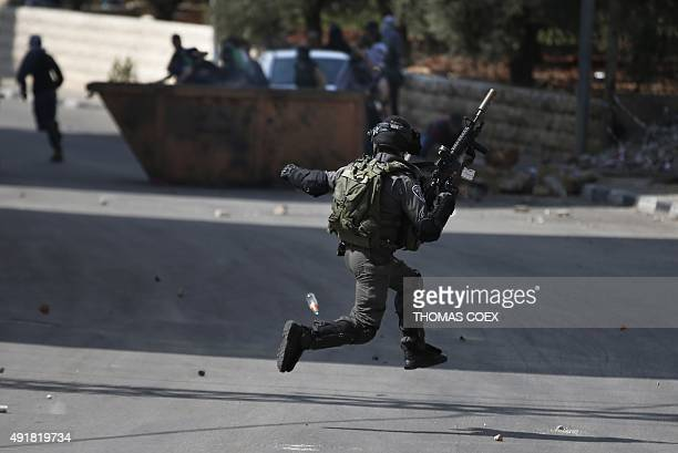 An Israeli security member runs as Palestinian demonstraters throw stones towards him during clashes in Beit El near the West Bank city of Ramallah...