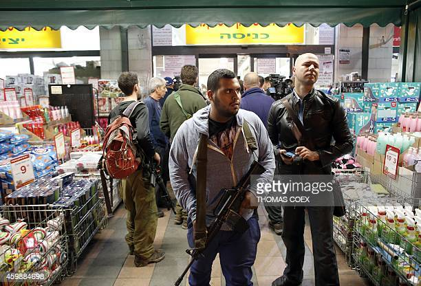 An Israeli security member stands guard at the entrance of a supermarket where a Palestinian teen stabbed two Israelis in 'an apparent terror attack'...