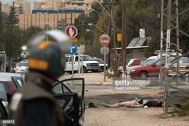 An Israeli security officer watches the body of a Palestinian gunman who was killed in a gun battle with Israeli security forces February 10 2002...