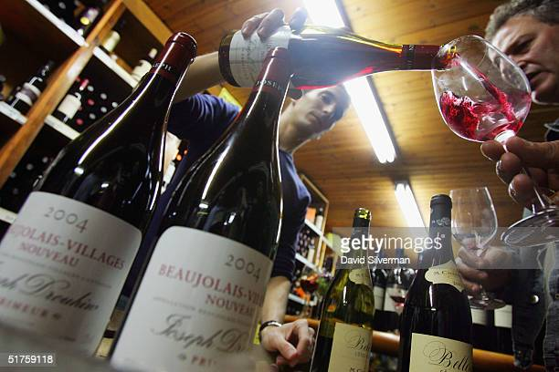 An Israeli serves French winemaker Joseph Drouhin's Beaujolais Nouveau 2004 at George Hinawi's liquor merchants moments after midnight November 18...