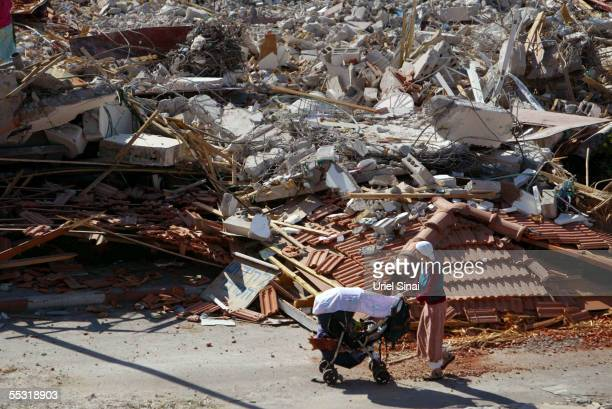 An Israeli settler and her baby walk past the rubble of demolished houses in the former Gaza Strip settlement of Neve Dekalim September 8 2005 in the...