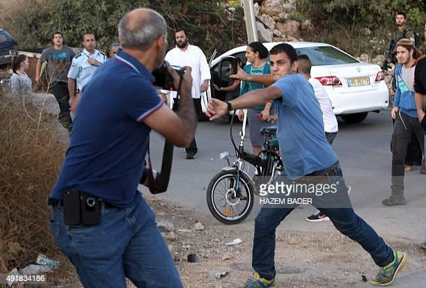 An Israeli settler attacks a Palestinian journalist near the Israeli settlement of Kiryat Arba near Hebron in the occupied West Bank on October 8...