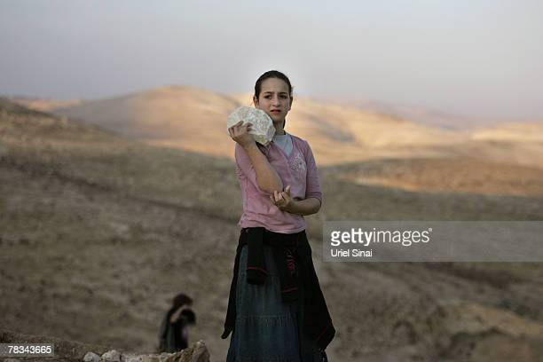 An Israeli settler caries a stone as settlers attempt to build a structure on the hills at the new E1 settlement area on December 9 2007 near the...