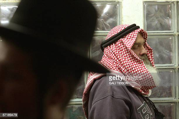 An Israeli settler dressed up as an Arab prays during the traditional reading of the scroll of Ester, 13 March 2006, at the West Bank settlement of...