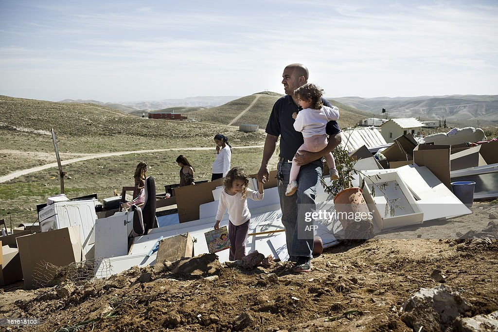 An Israeli settler holding his two daughters, one by the hand walks in front of the rubble of his house, demolished by Israeli police in the outpost of Maale Rehavam, in the Israeli occupied Palestinian West Bank, on February 13, 2013. The house was built without any authorization outside the larger state-sanctioned settlement. The number of Israeli settlers in the occupied West Bank grew by 4.7% in 2012, according to figures obtained by AFP from a settler organisation.