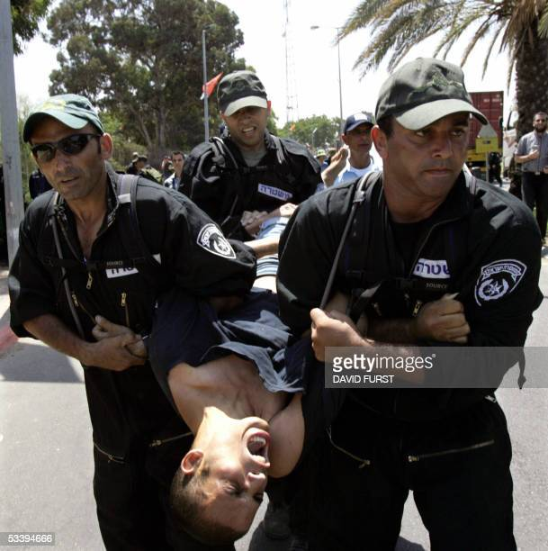 An Israeli settler is carried away by Israeli police officers after he and other protestors attempted to block the main road to the southern Gaza...