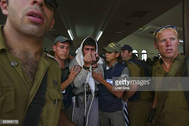 An Israeli settler is taken away from the Synagogue during evictions on August 17 2005 in Morag southern Gaza Strip Thousands of Israeli security...