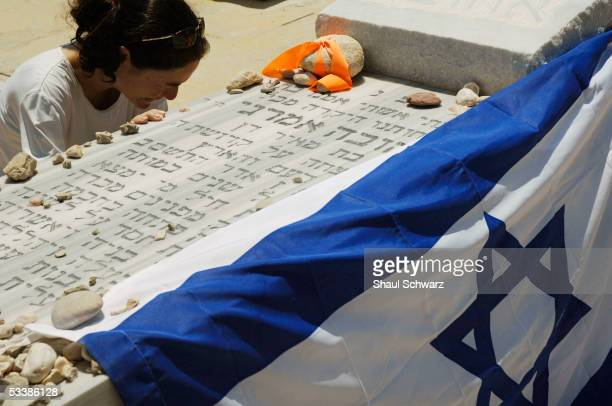 An Israeli settler prays at a relative's grave August 14 2005 at the regional cemetery at Neve Dekalim in the Gaza Strip Hundreds of residents of the...