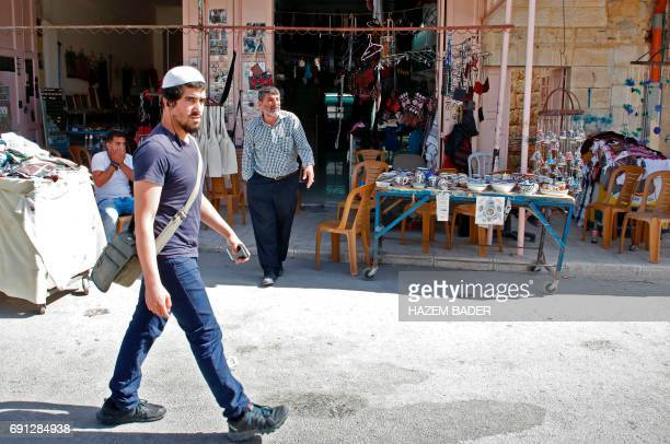 An Israeli settler walks past a Palestinian shop in the old city of Hebron on May 8 2017 in the Israeli occupied West Bank After half a century of...