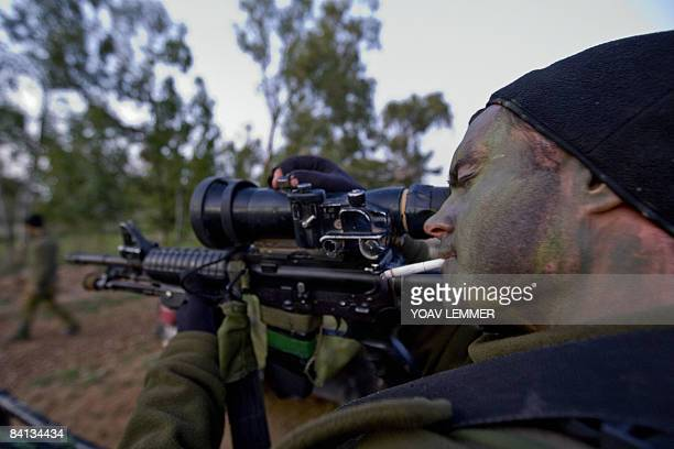 An Israeli sniper prepares his rifle as troops take position on the IsraeliGaza border on December 28 2008 Israeli tanks massed at the Gaza border...