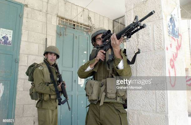 """An Israeli sniper takes aim April 6, 2002 during """"Operation Defensive Shield"""" in the West Bank town of Bethlehem. Israeli defense forces continued..."""
