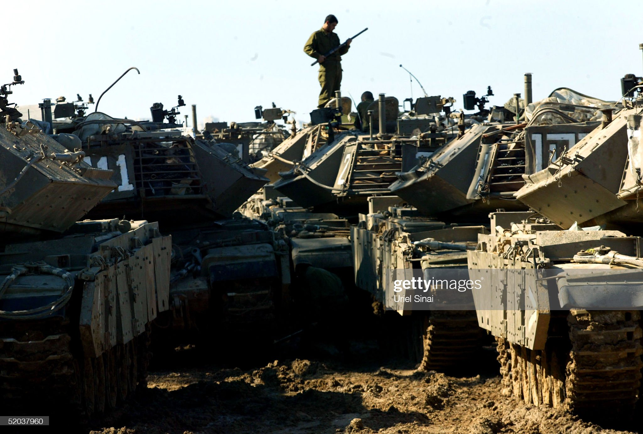 https://media.gettyimages.com/photos/an-israeli-sodier-inspects-a-column-of-parked-tanks-near-the-border-picture-id52037960?s=2048x2048