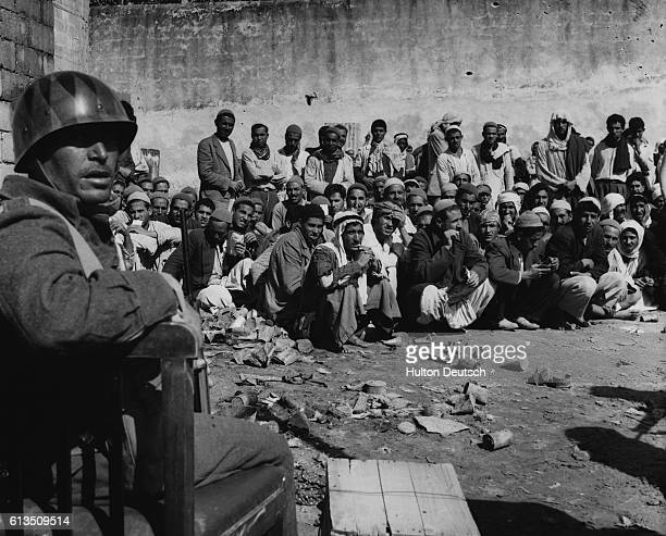 An Israeli solders watches captured Palestinians during the Suez Crisis 1956