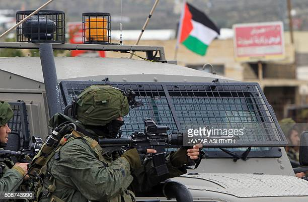 An Israeli soldier aims fire during clashes with Palestinian youths in the village of Qabatiya near the West Bank town of Jenin on February 6 2016...