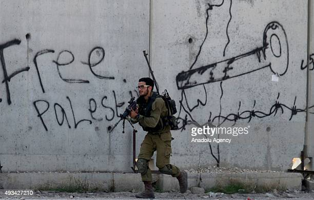 An Israeli soldier aims his rifle as Palestinians stage a protest against Israeli violations in Tulkarm West Bank on October 20 2015