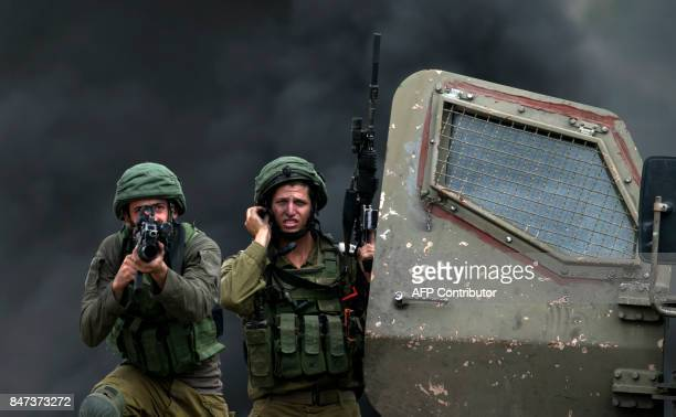 TOPSHOT An Israeli soldier aims his weapon during clashes with Palestinian protesters following a demonstration against the expropriation of...