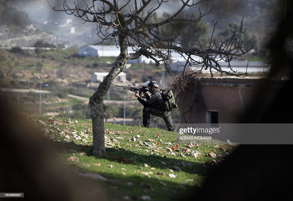 An Israeli soldier aims towards Palestinian protestors during clashes following a demonstration organised by residents of the West Bank village Nabi Saleh to protest against the expansion of Jewish settlements on Palestinian land on February 8, 2013.