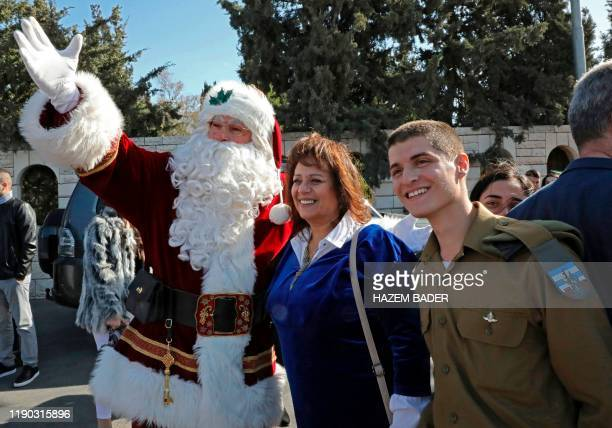 An Israeli soldier and a woman pose for a picture with a man dressed as Santa Claus at Israel's controversial separation barrier in the occupied West...
