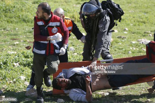 TOPSHOT An Israeli soldier attempts to detain an injured Palestinian demosntartor as he's carried on a stretcher by Palestinian Civil Defence...