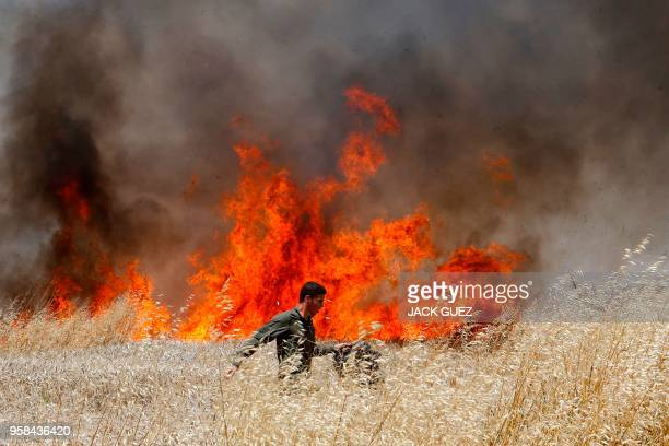 TOPSHOT An Israeli soldier attempts to extinguish a fire in a wheat field near the Kibbutz of Nahal Oz along the border with the Gaza strip on May 14...