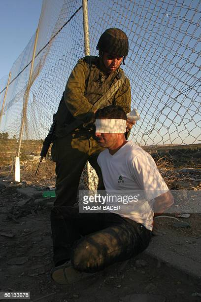 An Israeli soldier blindfolds an arrested Palestinian youth following a stonethrowing incident during a demonstration marking the first anniversary...