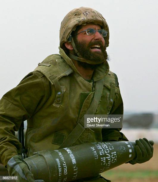 An Israeli soldier carries an artillery shell as his mobile artillery unit is deployed with orders to open fire against Palestinian militants in...