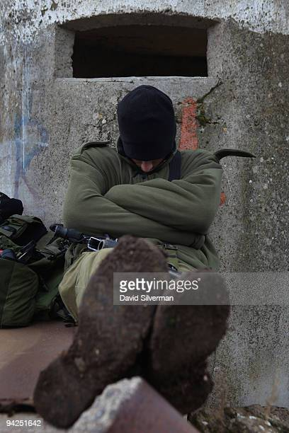 An Israeli soldier catches up his sleep against a pillbox after taking part in a livefire training exercise December 10 2009 on the Golan Heights The...