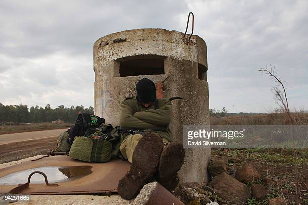 An Israeli soldier catches up on missed sleep against a pillbox after taking part in a livefire training exercise December 10 2009 on the Golan...