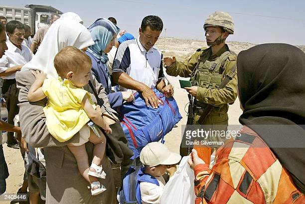 An Israeli soldier checks the ID of a Palestinian man August 17 2003 at an army checkpoint on the outskirts of the West Bank Palestinian town of...