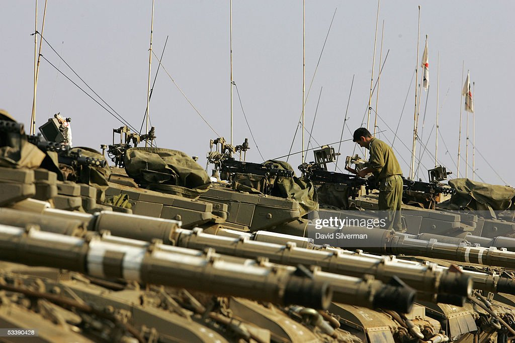 An Israeli soldier cleans the 0.5 inch caliber heavy machine guns on the turrets of Merkava tanks stationed near the border with the Gaza Strip August 15, 2005 in the fields of Kibbutz Mefalsim in southern Israel. The Israeli army has deployed hundreds of tanks and armored vehicles and thousands of troops to defend the Jewish state's historic withdrawal from the Gaza Strip after a 38-year occupation.