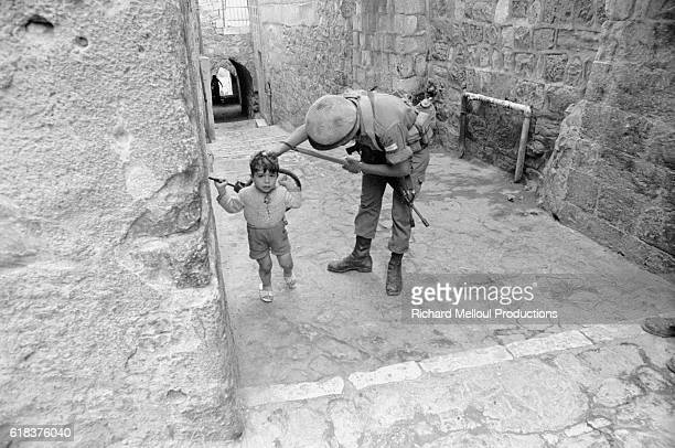 An Israeli soldier comforts a small child as word spreads through Israel that the Syrian army has just received a large delivery of arms. While Syria...
