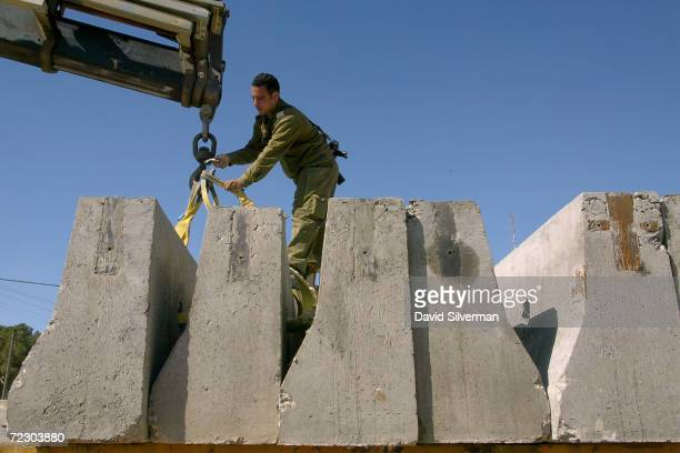 An Israeli soldier delivers concrete barriers to reinforce an army roadblock February 20 2002 in the West Bank town of Ramallah Israeli Prime...