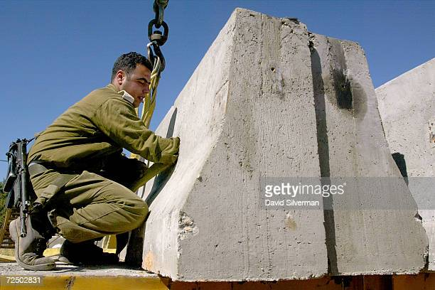 An Israeli soldier delivers concrete barriers to reinforce an army roadblock February 20, 2002 in the West Bank town of Ramallah. Israeli Prime...