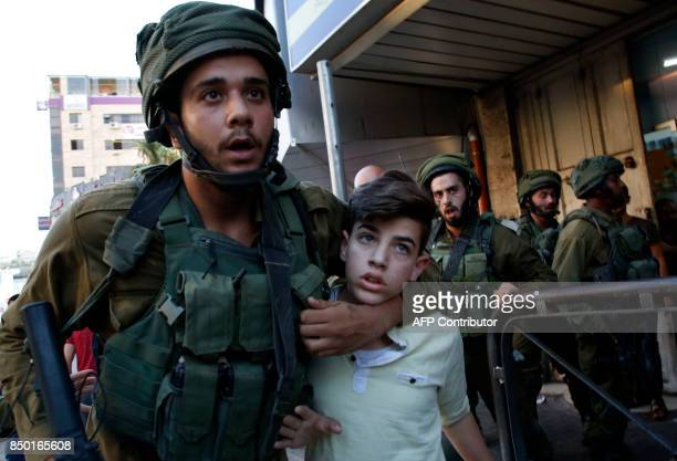 An Israeli soldier detains a Palestinian youth after troops entered an area controlled by the Palestinian authority in the divided city of Hebron in...