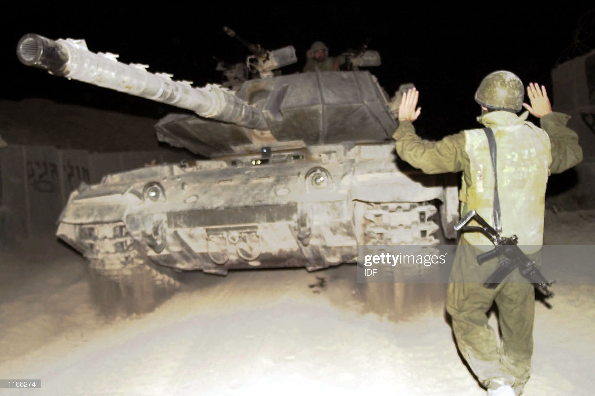 https://media.gettyimages.com/photos/an-israeli-soldier-directs-a-tank-as-it-withdraws-october-2-2001-to-picture-id1166274?s=2048x2048