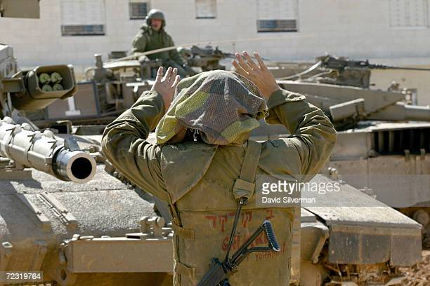 An Israeli soldier directs a tank into place near Palestinian leader Yasser Arafats headquarters February 20 2002in the West Bank town of Ramallah...